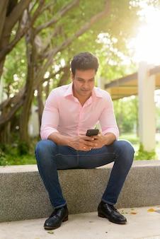 Pełny strzał ciała szczęśliwy młody przystojny indyjski biznesmen przy użyciu telefonu i siedząc w parku