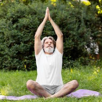 Pełny strzał człowiek robi joga