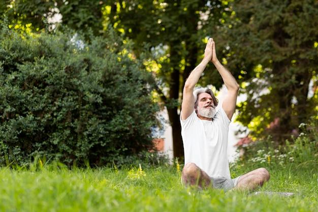 Pełny strzał człowieka na macie do jogi na zewnątrz