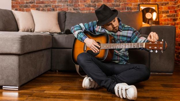 Pełny strzał człowieka na podłodze, grającego na gitarze