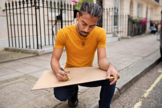 Pełny strzał człowieka piszącego na afiszu