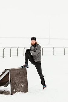 Pełny strzał człowieka rozciągającego się w śniegu