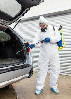 Pełny strzał człowieka z maską gazową dezynfekującą samochód