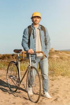 Pełny strzał człowieka z rowerem na plaży