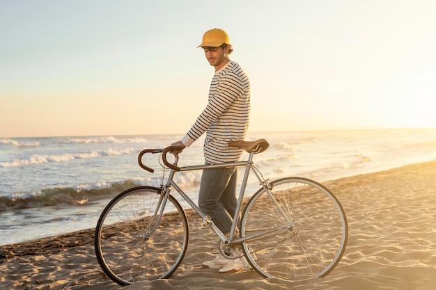 Pełny strzał człowieka z rowerem nad morzem
