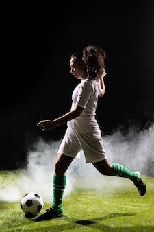 Pełny strzał dysponowana kobieta bawić się piłkę nożną