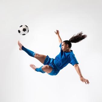 Pełny strzał dysponowana kobieta kopie piłkę