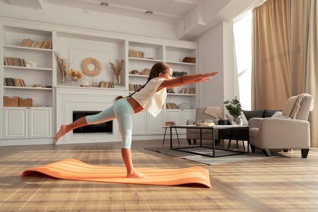 Pełny strzał dzieciak robi jogę w domu?