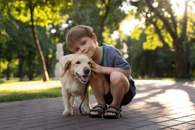 Pełny strzał dziecko i pies w parku