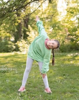Pełny strzał dziewczyna ćwiczenia na świeżym powietrzu
