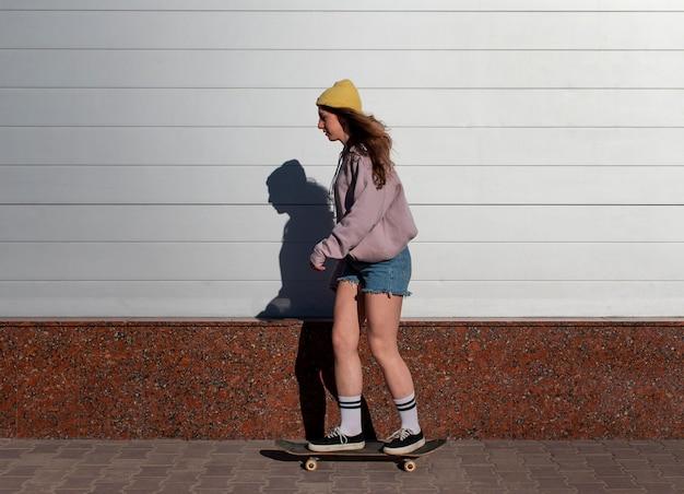 Pełny strzał dziewczyna na łyżwach na świeżym powietrzu