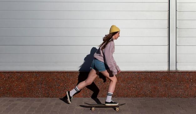 Pełny strzał dziewczyna na łyżwach na zewnątrz