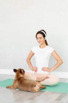 Pełny strzał dziewczyna na macie do jogi z psem