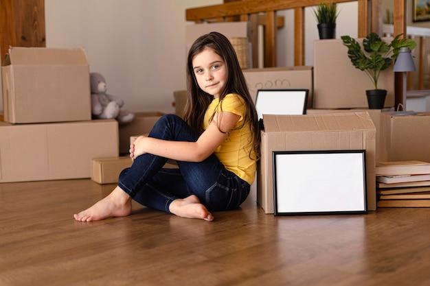 Pełny strzał dziewczyna pozuje z pudełkiem