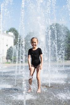 Pełny strzał dziewczyna przy wodną fontanną