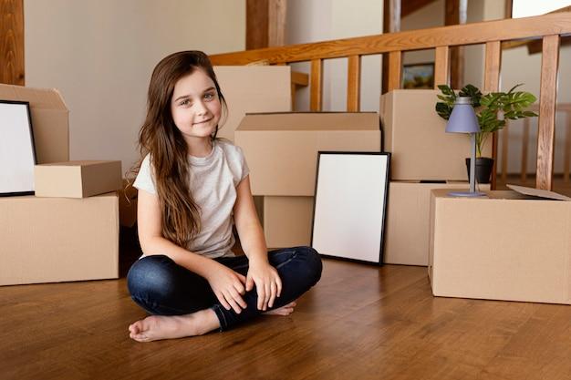 Pełny strzał dziewczyna siedzi na pudełku