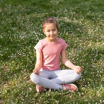 Pełny strzał dziewczyna siedzi na trawie
