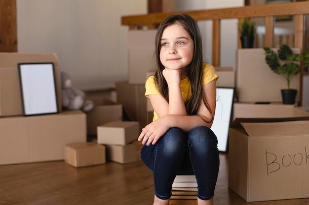 Pełny strzał dziewczyna siedzi w pomieszczeniu