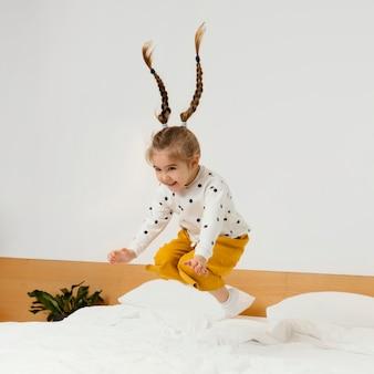 Pełny strzał dziewczyna skacząca na łóżku