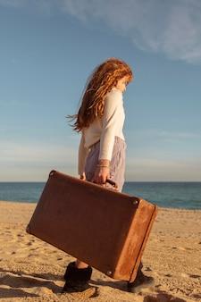 Pełny strzał dziewczyna trzyma walizkę