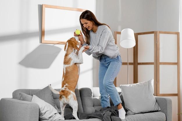 Pełny strzał dziewczyny i psa stojącego na kanapie