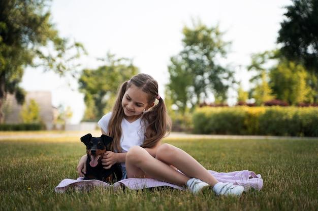 Pełny strzał dziewczyny pieszczący psa