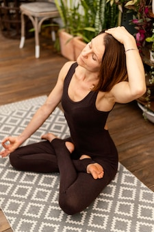 Pełny strzał fit kobieta na macie do jogi