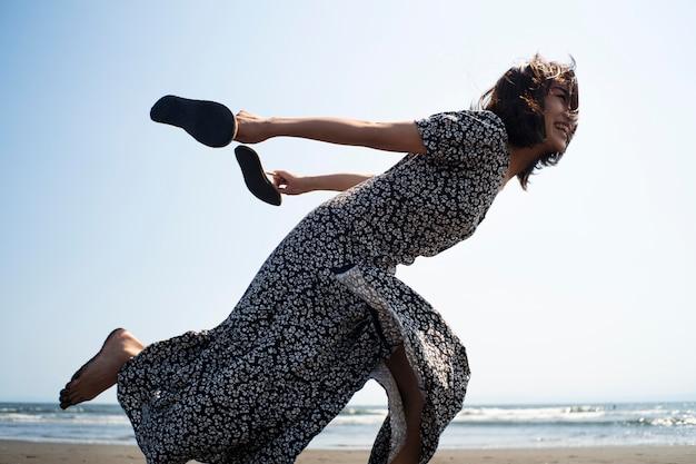 Pełny strzał japońskiej kobiety biegającej na plaży?