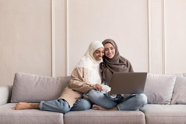 Pełny strzał kobiet siedzących na kanapie z laptopem