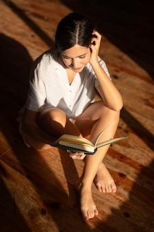 Pełny strzał kobieta czytająca na podłodze