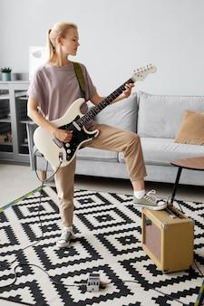 Pełny strzał kobieta grająca na gitarze w domu