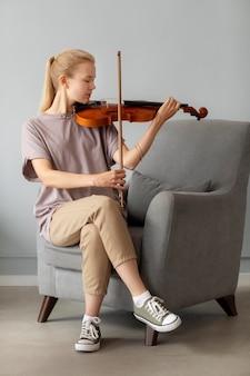 Pełny strzał kobieta grająca na skrzypcach