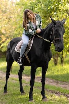 Pełny strzał kobieta jedzie na koniu