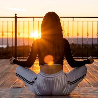 Pełny strzał kobieta medytacji o zachodzie słońca