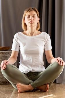 Pełny strzał kobieta medytuje na podłodze