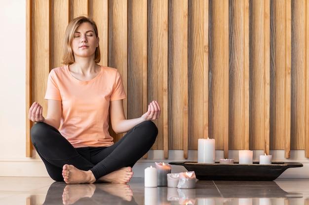 Pełny strzał kobieta medytuje przy świecach