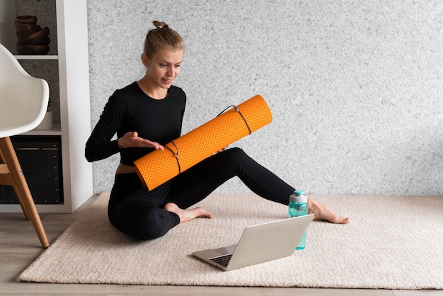 Pełny strzał kobieta na dywanie z laptopem