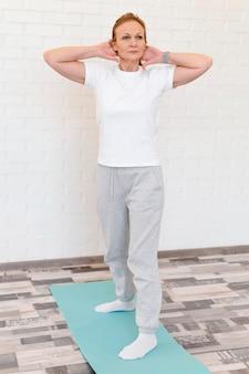 Pełny strzał kobieta na macie do jogi