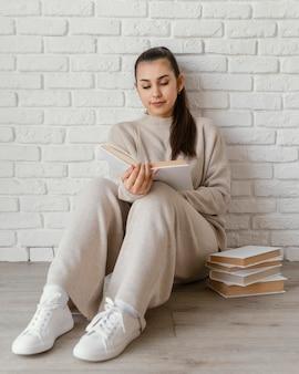 Pełny strzał kobieta na podłodze czytania książki