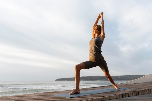 Pełny Strzał Kobieta Praktykuje Jogę Na Macie W Pobliżu Morza Darmowe Zdjęcia
