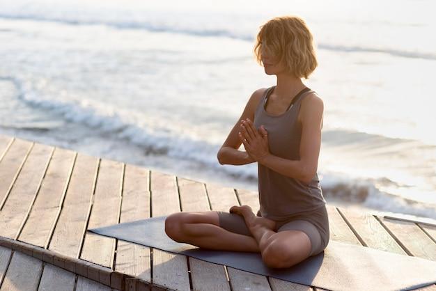 Pełny strzał kobieta praktykuje jogę z morzem w tyle