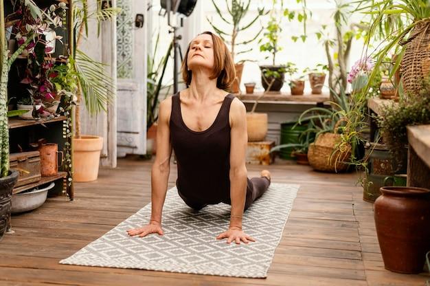 Pełny strzał kobieta robi joga na macie