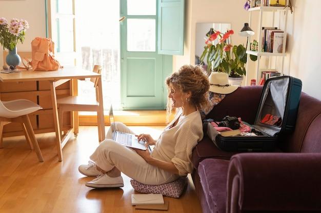 Pełny strzał kobieta siedząca z laptopem