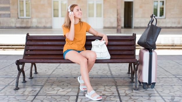 Pełny strzał kobieta, słuchanie muzyki na ławce w stacji kolejowej