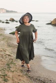 Pełny strzał kobieta spaceru na plaży