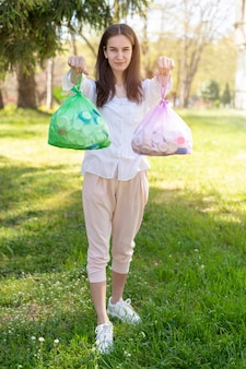 Pełny strzał kobieta trzyma plastikowe torby z śmieci