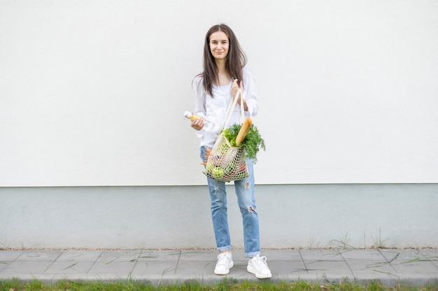 Pełny strzał kobieta trzyma torby wielokrotnego użytku poza