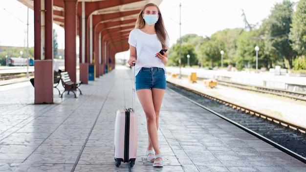 Pełny strzał kobieta ubrana w maskę z bagażem na stacji kolejowej