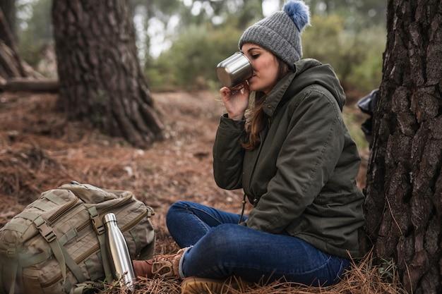 Pełny strzał kobieta w pobliżu drzewa do picia