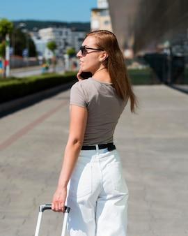 Pełny strzał kobieta z bagażem rozmawia przez telefon na stacji